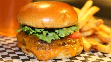 close up of cheeseburger, fries, and beer