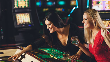 2 ladies playing a game at the casino