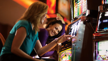2 ladies playing at the slot machine
