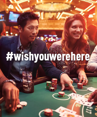 "man and woman playing blackjack with text ""#WishYouWereHere"""
